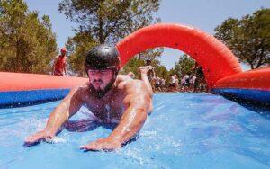 chico deslizandose en un tobogan de agua en una fiesta de humor amarillo organizada en Valencia