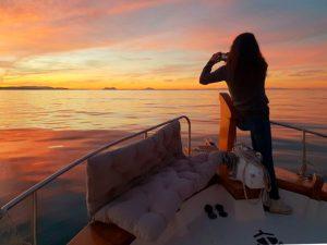 chica contemplando la puesta sobre un barco en Dénia