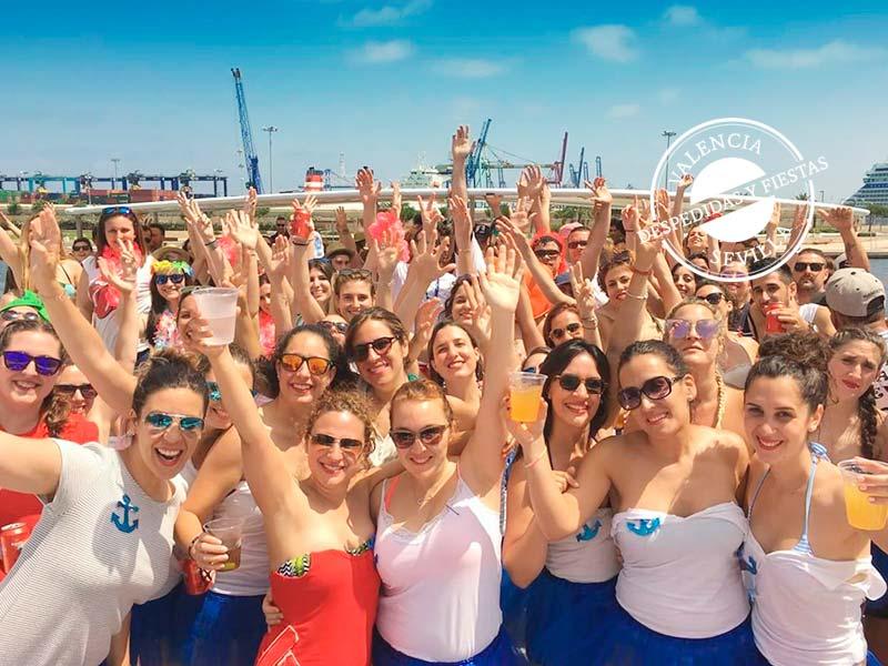 grupo de personas disfrutando de comida y fiesta en barco en Valencia